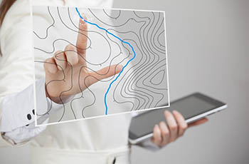 Woman scientist working with futuristic GIS interface on a transparent screen